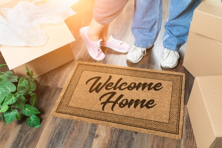Man and Woman Unpacking Near Welcome Home Welcome Mat, Moving Boxes and Plant.